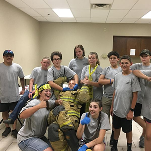 CPR students standing around a manikin dressed in a Fire fighters uniform
